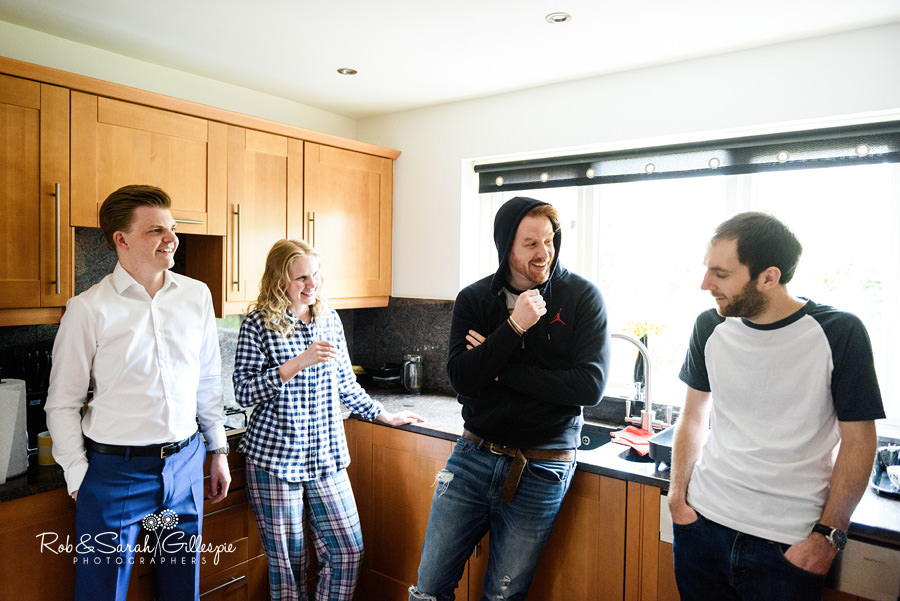 Groom and friends chat in kitchen before getting ready for wedding