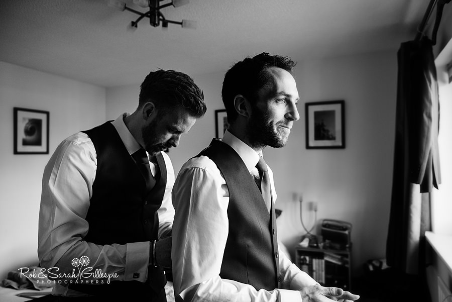 Best-Man helps groom get ready for wedding in strong window light