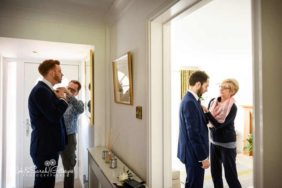 Best-Man and groom have ties fixed by parents