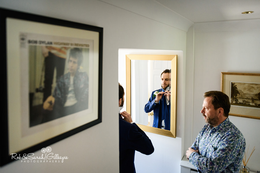 Groom fixes tie in mirror while father watches