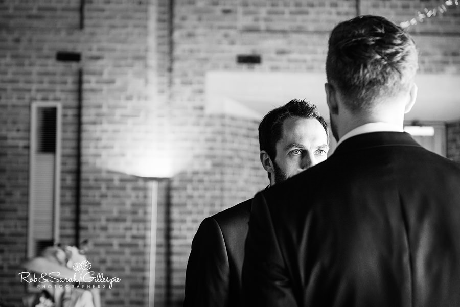 Groom chats with best man before wedding ceremony in Guesten Hall