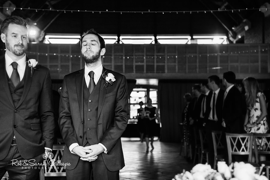 Groom looking nervous as bride and bridesmaids make their entrance to wedding ceremony
