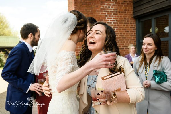 Wedding guest hugs bride at Avoncroft Museum wedding