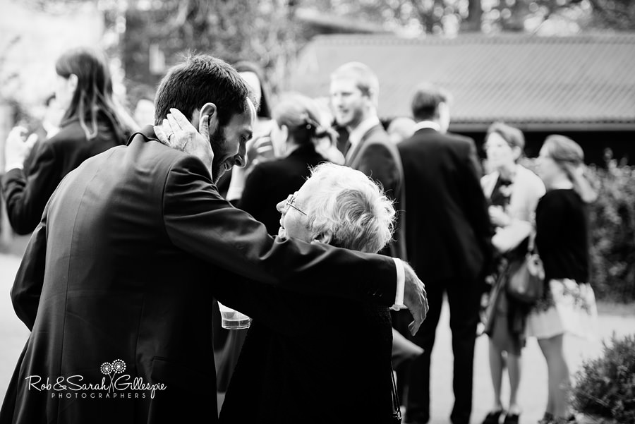 Wedding guests congratulate bride and groom outside at Avoncroft Museum wedding