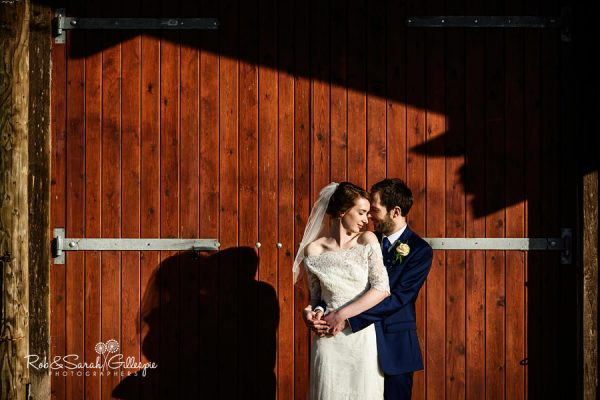 Bride and grom in front of Avoncroft barn doors