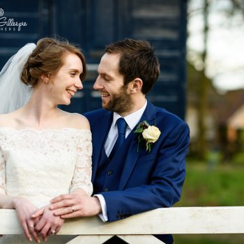 Bride & groom smiling at each other leaning on gate at Avoncroft Museum