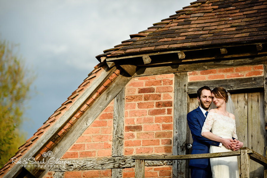 Bride and groom together with old buildings at Avoncroft Museum wedding