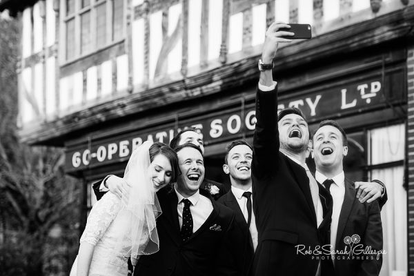 Bride, groom and friends laughing at Avoncroft Museum wedding