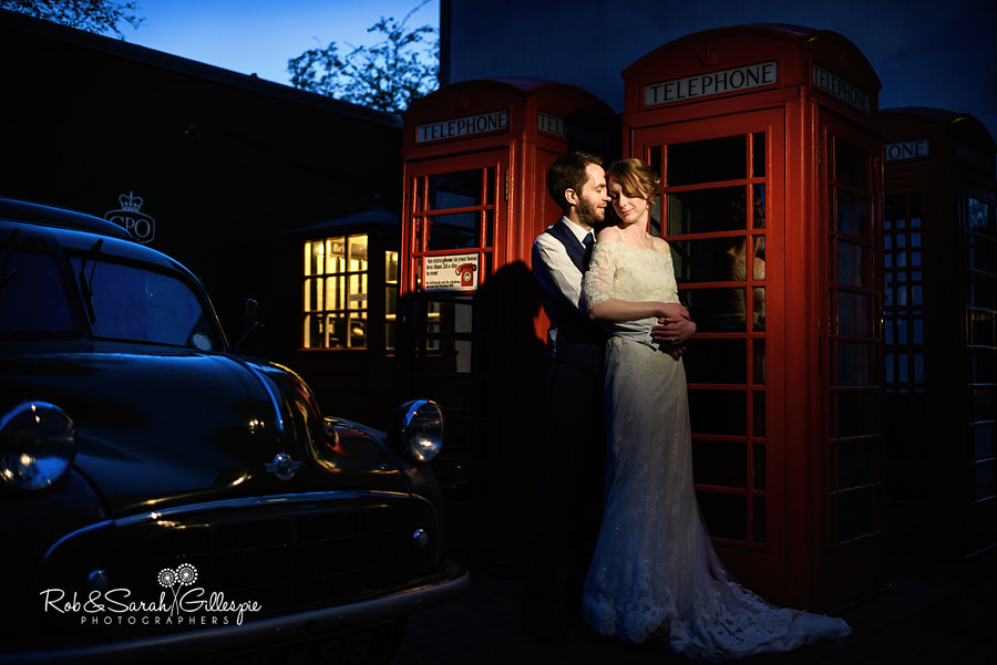 Bride and groom together near telephone boxes at Avoncroft Museum