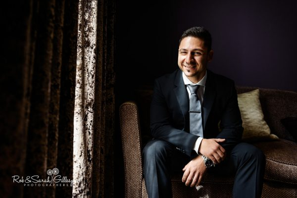 Portrait of groom sitting in window light at Hogarths Solihull