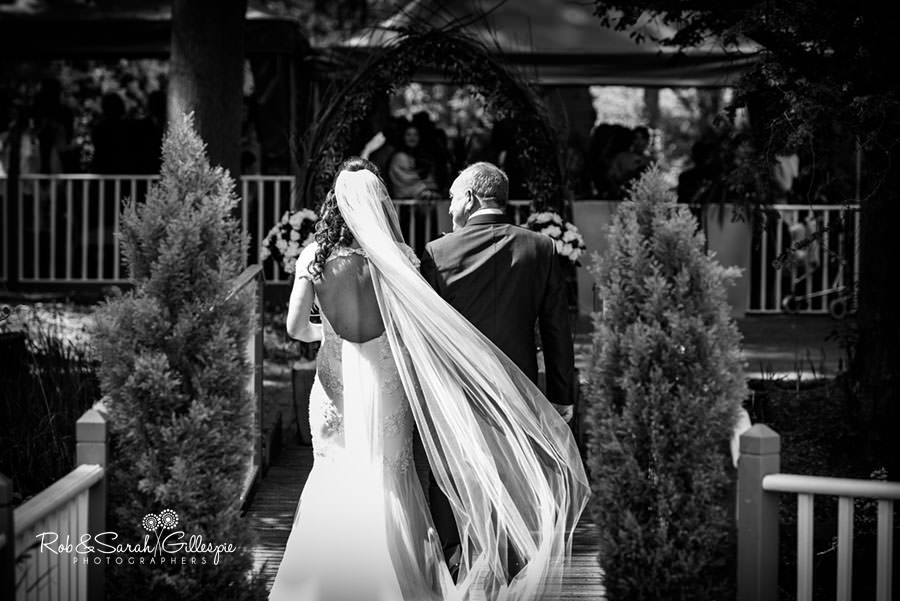 Bride and father walking towards outdoor wedding ceremony at Hogarths