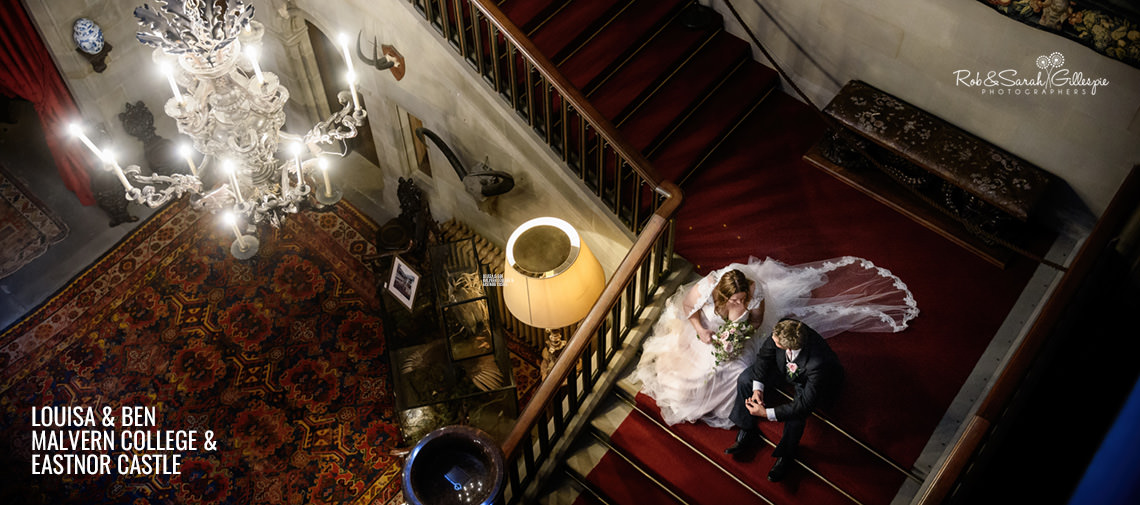 Bride and groom sitting on stairway at Eastnor Castle