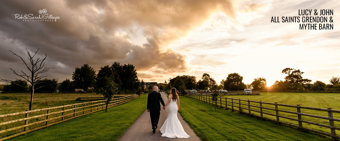 Bride and groom walking together under dramatic sky at Mythe Barn