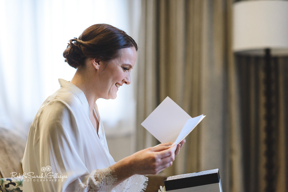 Bride reads card from groom while getting ready for wedding at Hampton Manor