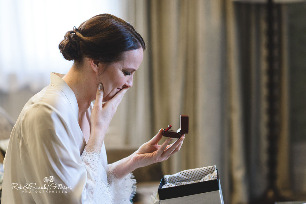 Bride reacts to gift from groom while getting ready for wedding at Hampton Manor