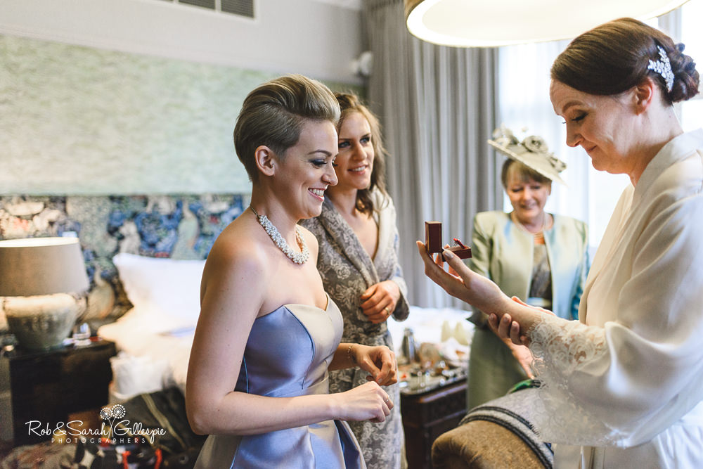 Bridemaids reacts to gift from groom while getting ready for wedding at Hampton Manor
