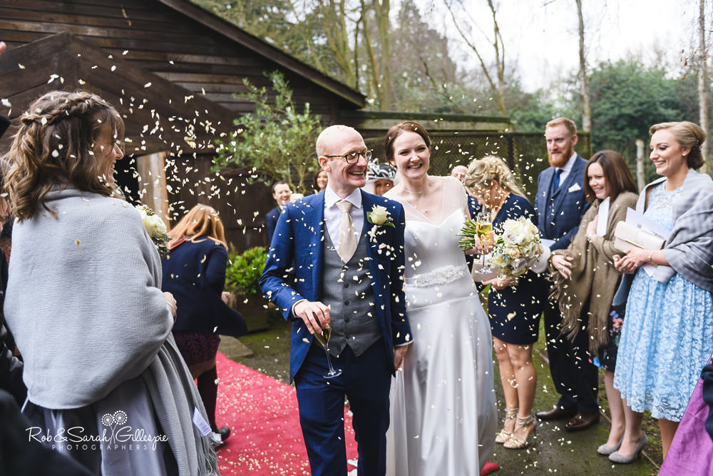 Wedding guests congratulate bride and groom and throw confetti at Hampton Manor