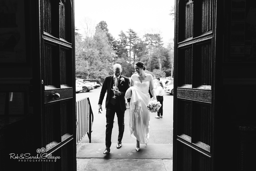 Bride and groom walk through Hampton Manor entrance laughing