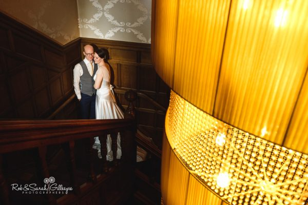Bride and groom on stairway at Hampton Manor