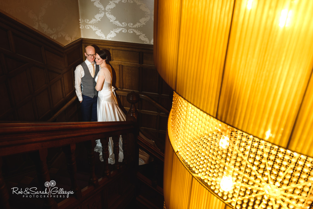 Bride and groom at Hampton Manor on staircase
