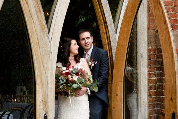 Bride and groom in arched doorway at Shustoke Barn