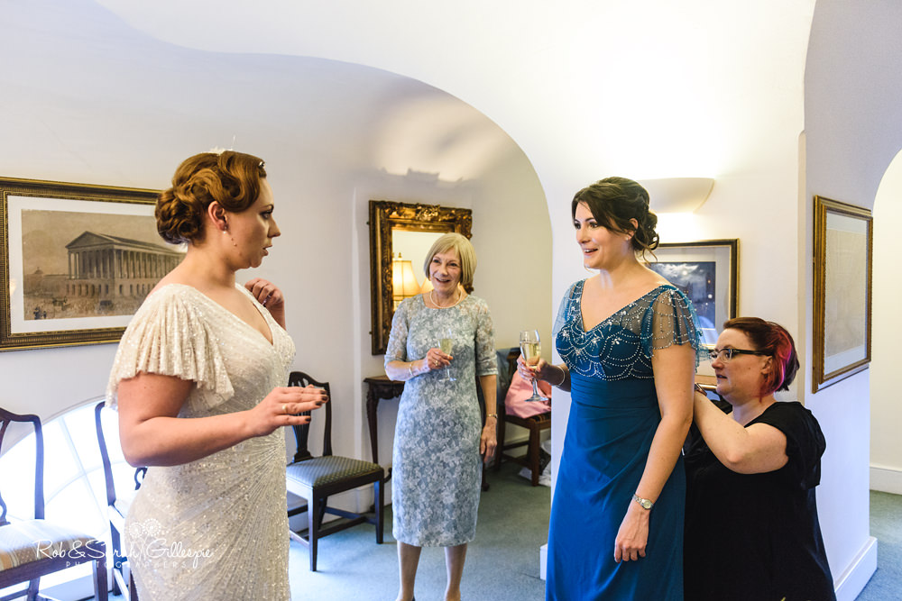 Bridesmaid and bride chat while getting ready for wedding at Birmingham Town Hall