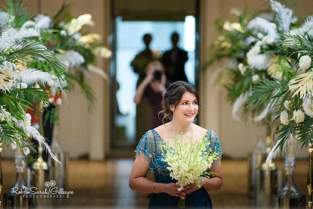 Bridesmaid makes entrance to civil wedding ceremony at Birmingham Town Hall, smiling at guests