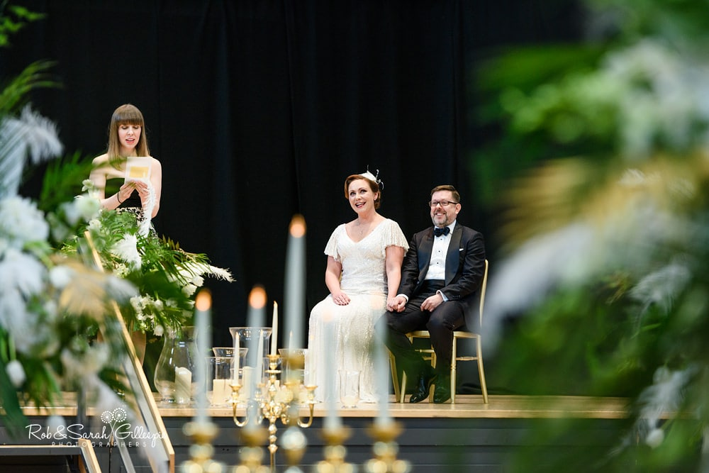 Bride and groom smile as wedding guests does a reading at Birmingham Town Hall