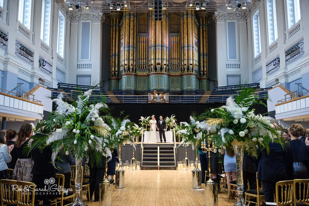Wide view of Birmingham Town Hall interior as bride and groom face clapping gests,