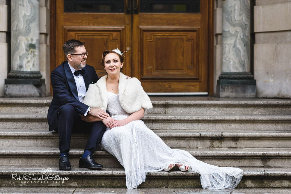 Bride and groom sitting on steps under ornate doorway at Birmingham Museum and Art Gallery