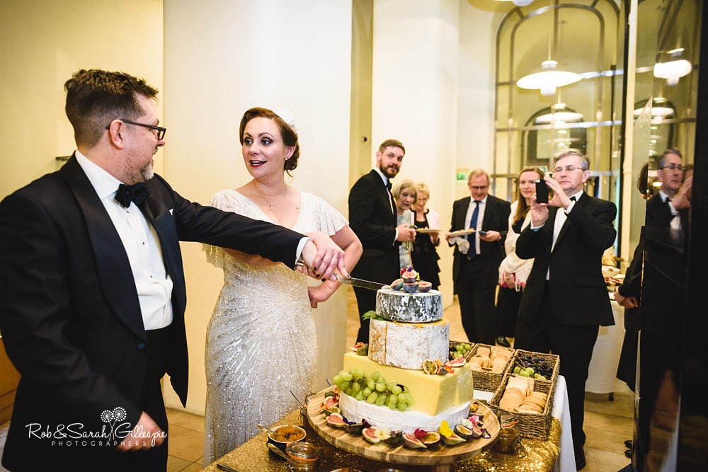 Bride and groom cut wedding cheese cake at Birmingham Town Hall wedding