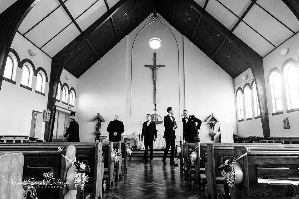 Groom and usehrs prepare for wedding at St Annes RC church Streetly