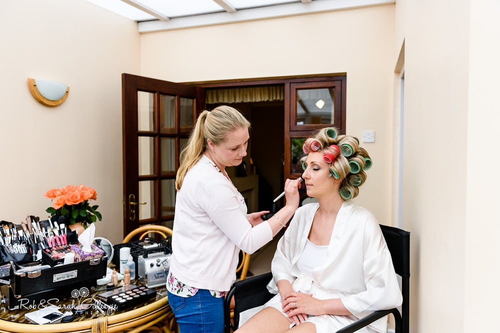 Bride with hair in curlers having makeup applied