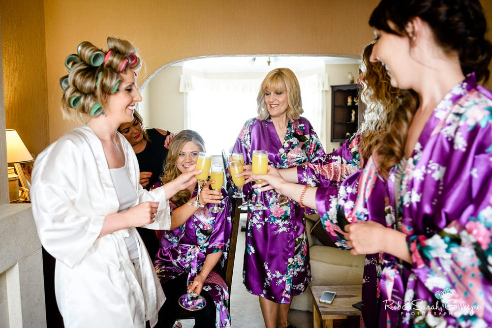 Bride and bridesmaids say cheers