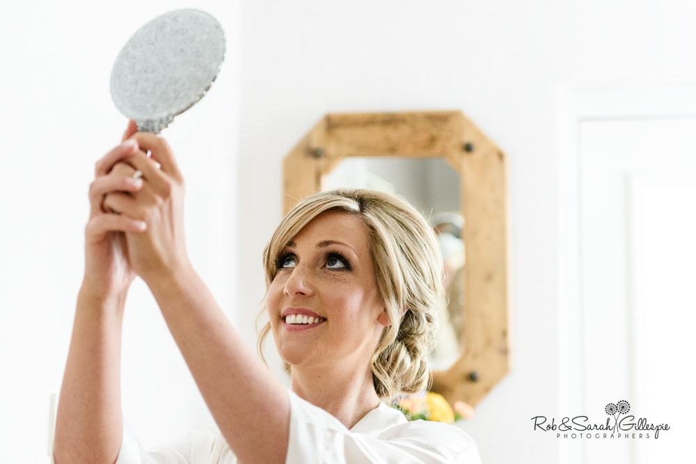 Bride checks hair in the mirror