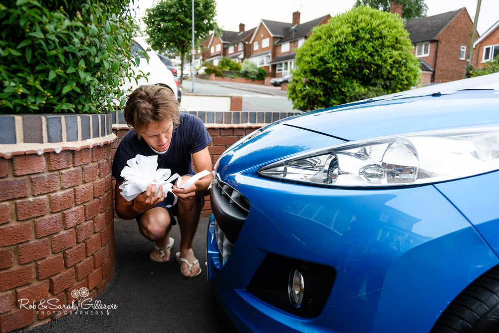 Groom watches as friends decorate cars for wedding