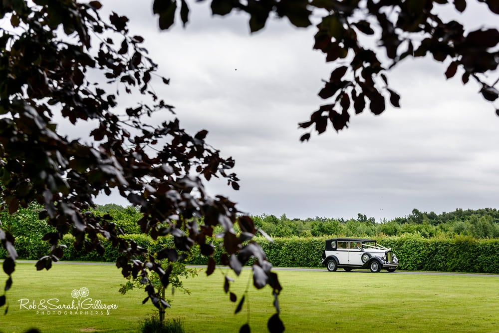 Bride gets out of wedding car at Alrewas Hayes