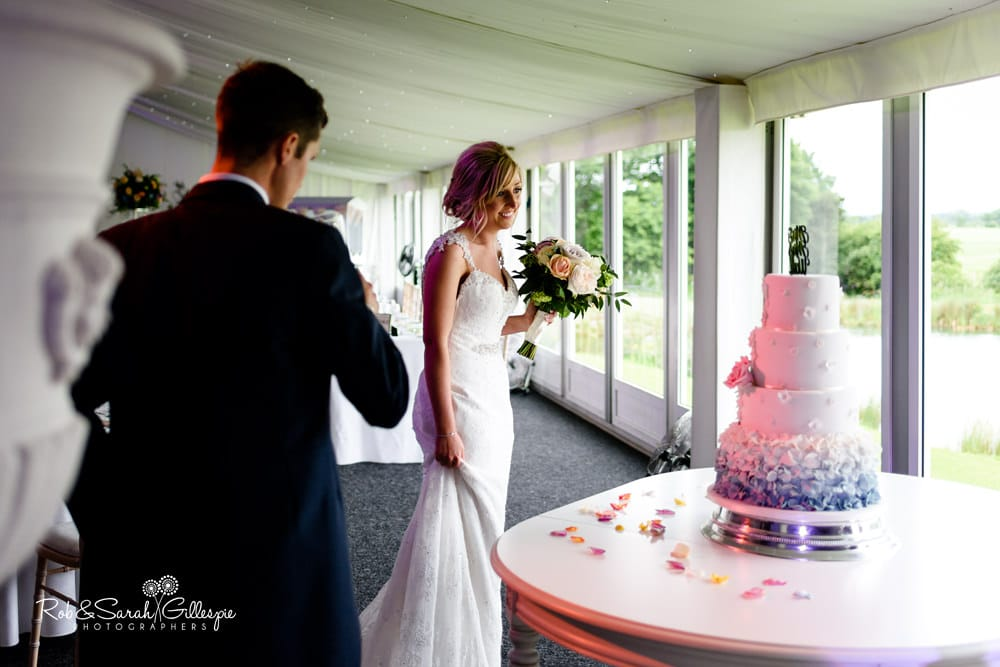 Bride and groom look at wedding cake at Alrewas Hayes