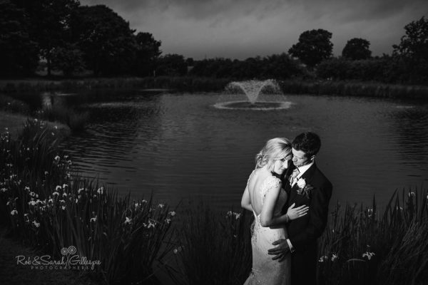 Bride and groom by lake at Alrewas Hayes with fountain in background