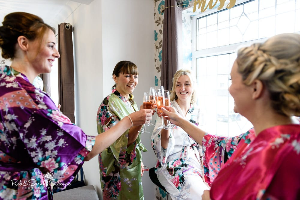 Bride, bridesmaids and mum say cheers