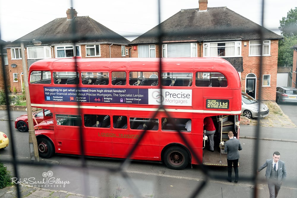 Red double-decker bus pulls up outside Bride's home to take her to wedding