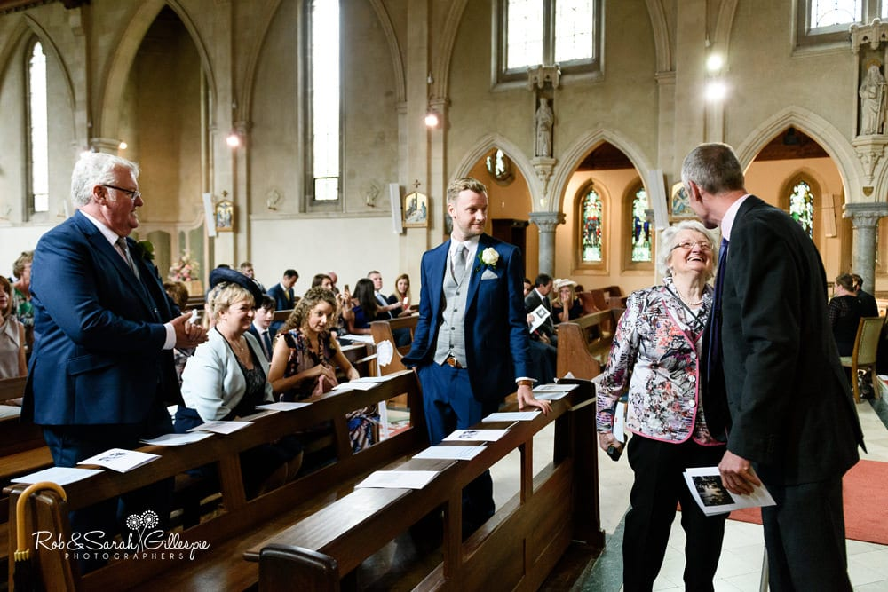 Groom greets wedding guests at Olton Friary