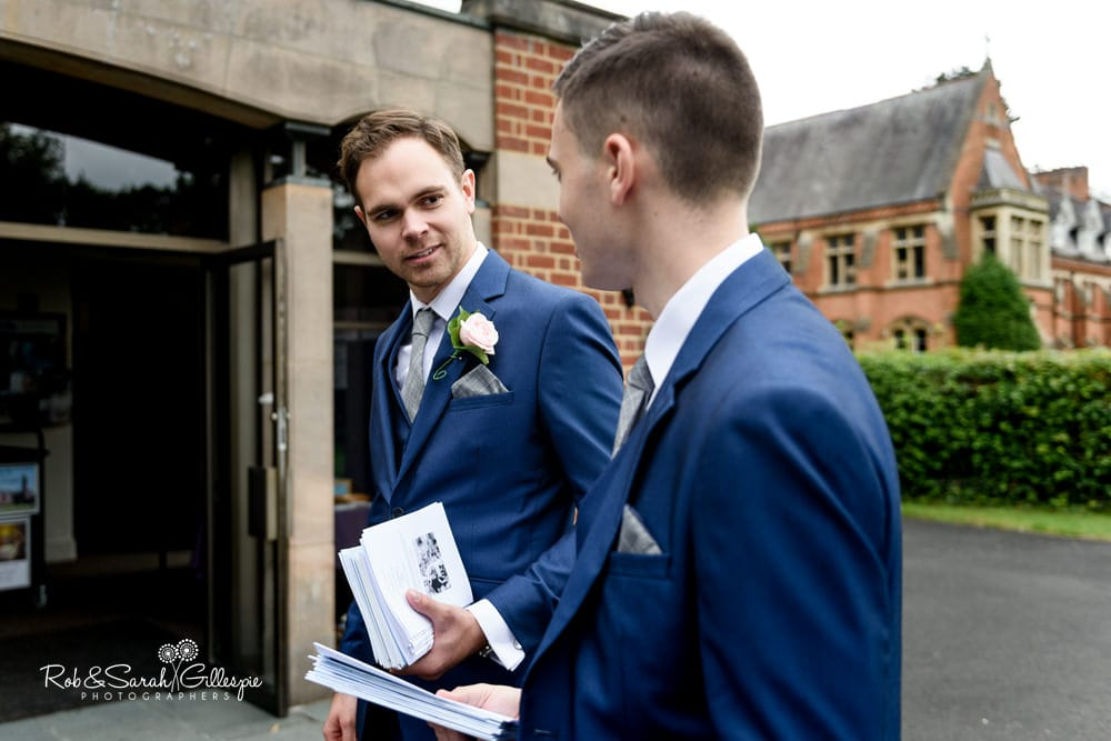 Groomsmen hand out order of service at Olton Friary
