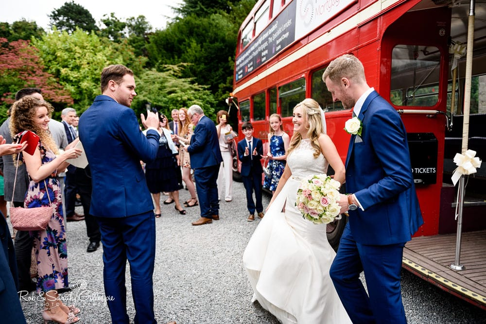 Bride and groom arrive at New Hall Hotel on red double decker bus