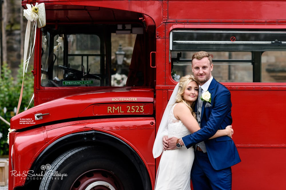 Bride and groom next to red double decker bus at New Hall Hotel