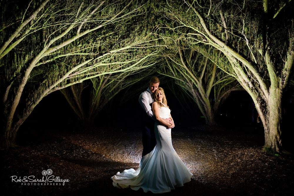 Bride and groom under avenue of trees at New Hall Hotel