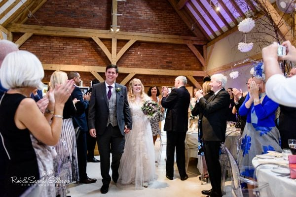 Bride and groom enter wedding breakfast at Redhouse Barn
