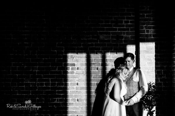 Bride and groom in dramatic light at Redhouse Barn