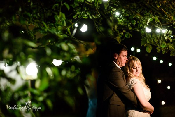 Bride and groom in Redhouse Barn gardens at night