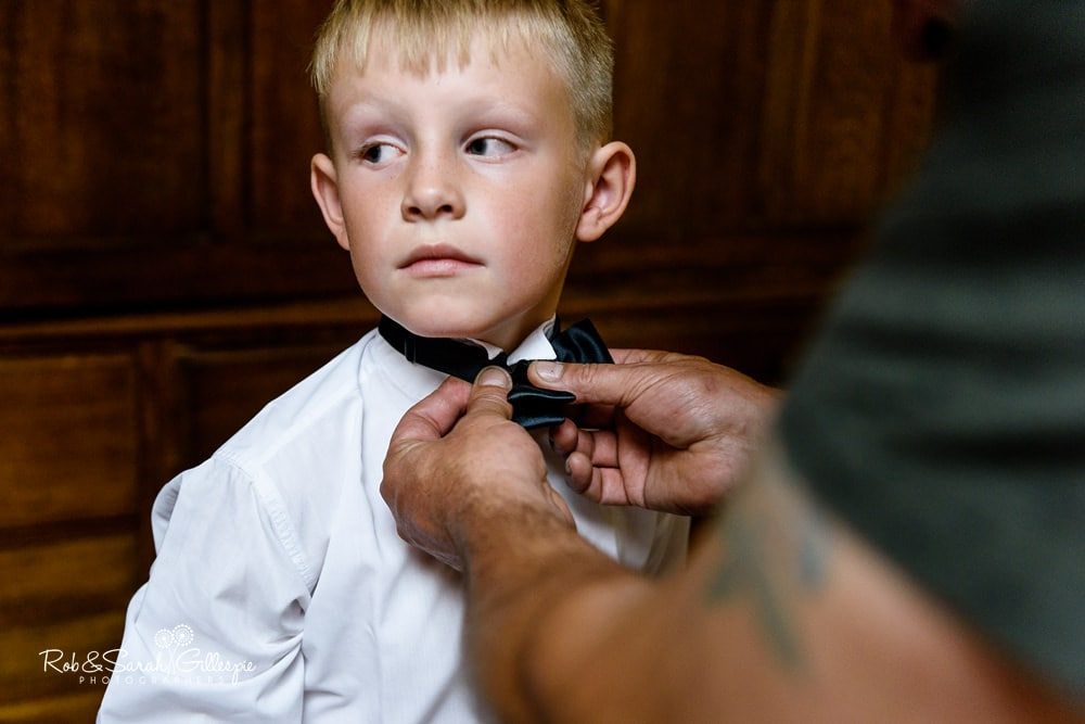 Pageboy has tie adjusted before wedding at Stanbrook Abbey Hotel